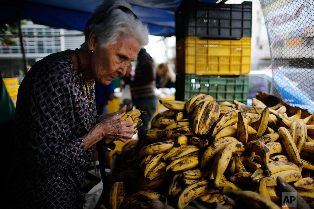 A woman pick out plantains at a market, Aug. 23, 2017, Caracas, Venezuela. (AP Photo/Ariana Cubillos)