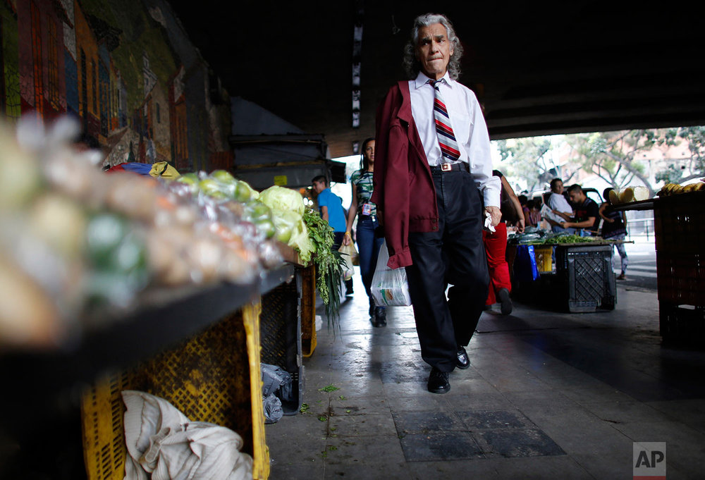 A man walks past vegetables for sale, Aug. 23, 2017,  Caracas, Venezuela. (AP Photo/Ariana Cubillos)