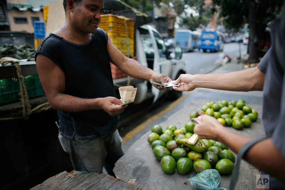 A street vendor sells avocados, Aug. 23, 2017, Caracas, Venezuela. Venezuelan President Nicolas Maduro has been celebrating calm returning to the streets after months of deadly protests, yet the country's imploding economy poses an ever more severe threat. (AP Photo/Ariana Cubillos)