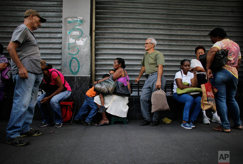 People wait outside a supermarket for subsidized products to arrive, Aug. 23, 2017, Caracas, Venezuela. (AP Photo/Ariana Cubillos)