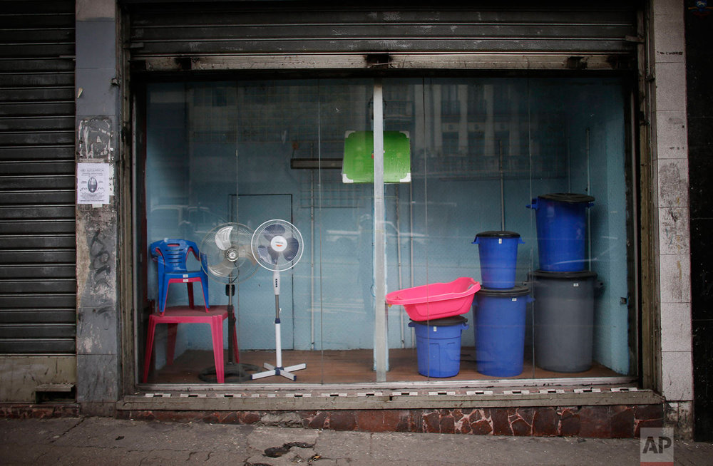 A shop window shows the few products it has for sale, Aug. 23, 2017, in downtown Caracas, Venezuela. U.S. economic sanctions on Venezuela make it more likely Venezuela will stop payment on its debt, or reduce what few goods it still imports. (AP Photo/Ariana Cubillos)