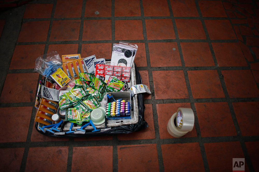 A street vendor's basket full of cigarette lighters, razors, batteries, insect killer, tape, glue, hair nets, lotion and sink filters, sits on the sidewalk, Aug. 23, 2017,  downtown in Caracas, Venezuela. (AP Photo/Ariana Cubillos)
