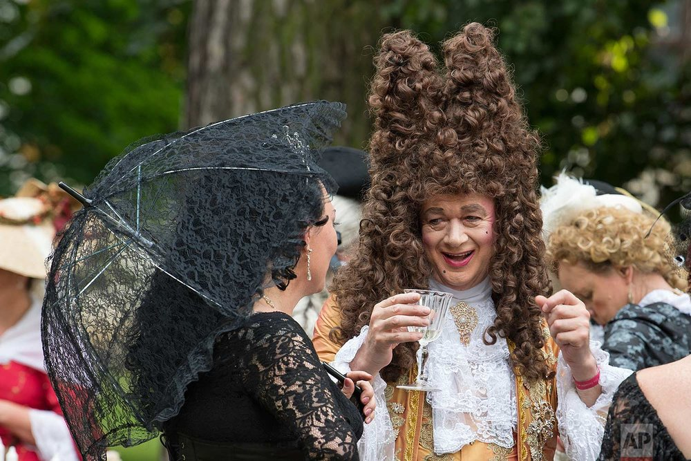 People in period costumes talk outside the Friedenstein Castle at the Baroque Festival in Gotha, Germany, Saturday, Aug. 26, 2017. (AP Photo/Jens Meyer)