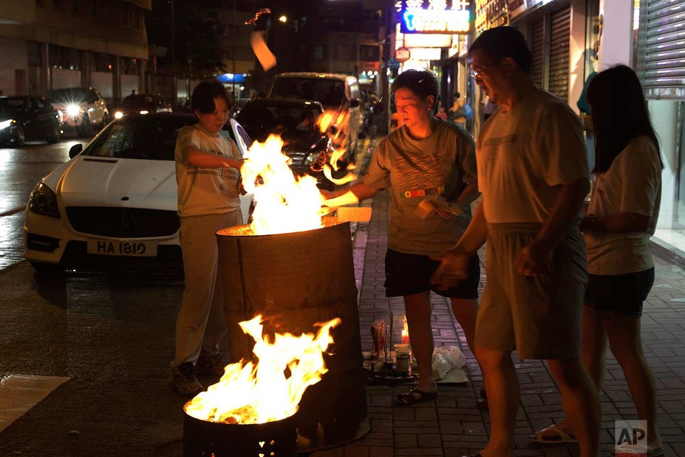 "In this Aug. 31, 2017, photo, a family burns paper money – locally known as ""Hell Money"" – during the ""Hungry Ghost Festival"" on a street in Hong Kong. (AP Photo/Kin Cheung)"