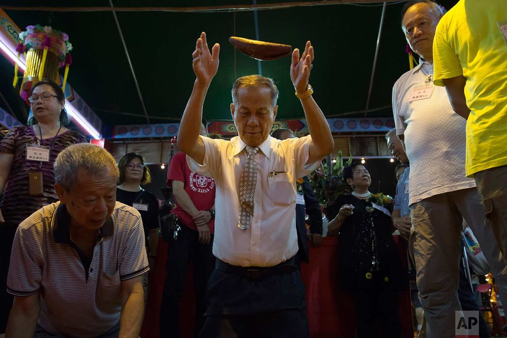 "In this Sept. 3, 2017, photo, a man throws wooden moon blocks to request an answer from the gods, at a makeshift altar during the ""Hungry Ghost Festival"" in Hong Kong. (AP Photo/Kin Cheung)"