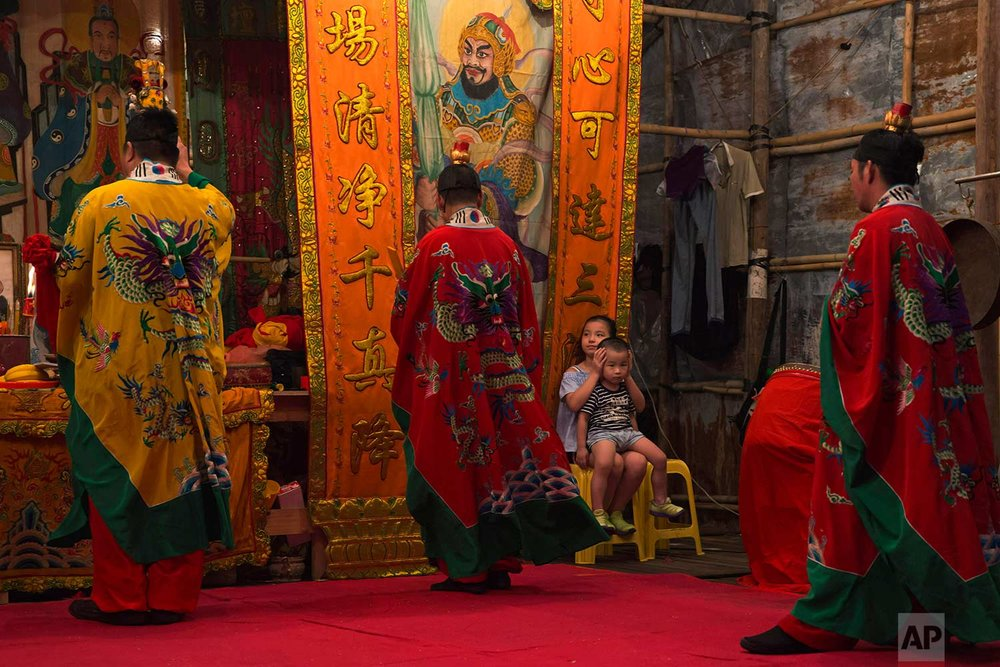 "In this Sept. 2, 2017, photo, Taoists attend a service at a makeshift theater during the ""Hungry Ghost Festival"" in Hong Kong. (AP Photo/Kin Cheung)"