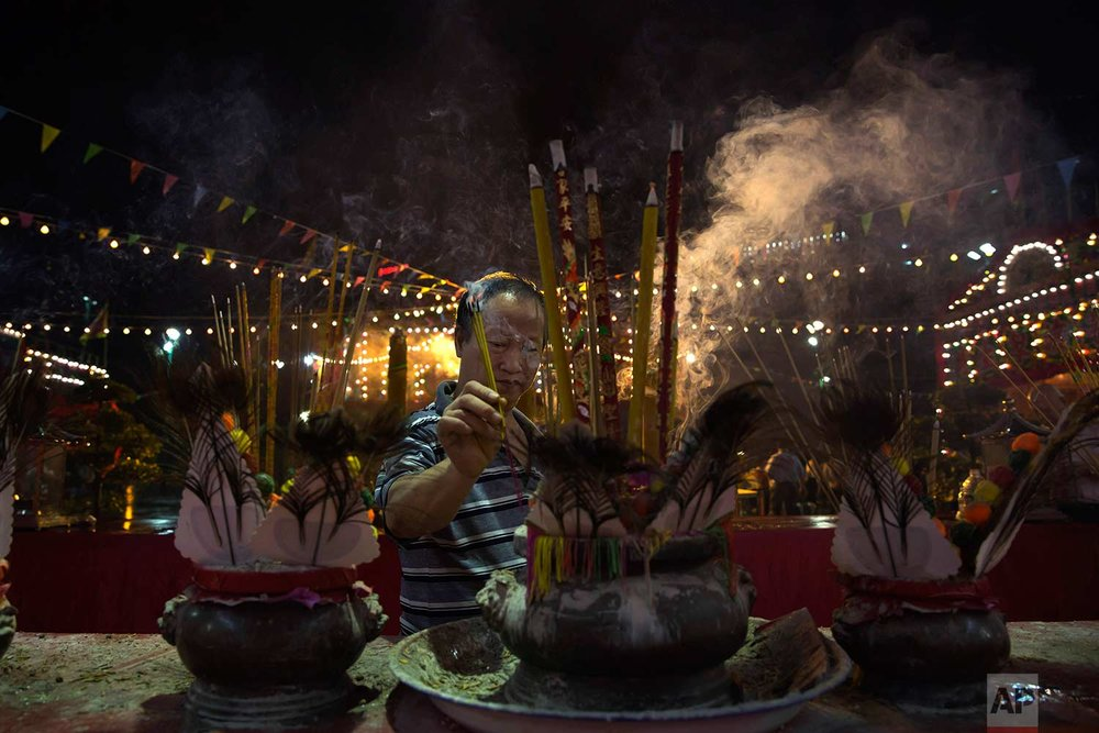 "In this Sept. 3, 2017, photo, a worshiper burns incense during the ""Hungry Ghost Festival"" in Hong Kong. (AP Photo/Kin Cheung)"