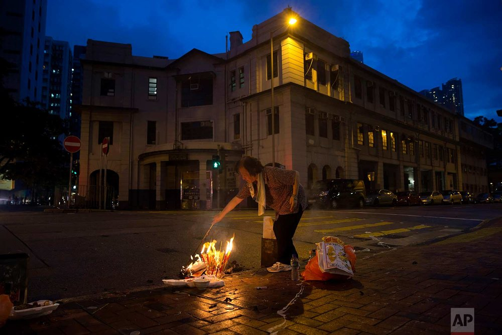 "In this Sept. 4, 2017, photo, a woman burns paper money – locally known as ""Hell Money"" – during the ""Hungry Ghost Festival"" on a street in Hong Kong. (AP Photo/Kin Cheung)"
