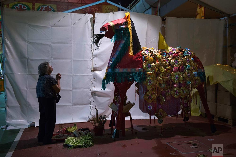 "In this Aug. 31, 2017, photo, a worshiper prays in front of a paper horse effigy during the ""Hungry Ghost Festival"" in Hong Kong. (AP Photo/Kin Cheung)"