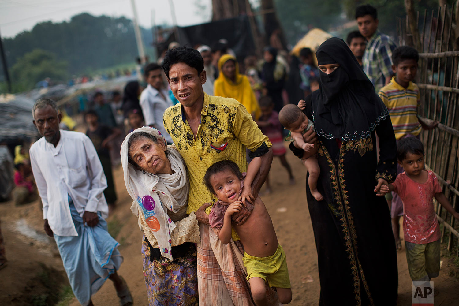 An exhausted Rohingya helps an elderly family member and a child as they arrive at Kutupalong refugee camp after crossing from Myanmmar to the Bangladesh side of the border, in Ukhia, Tuesday, Sept. 5, 2017. The man said he lost several family members in Myanmar. Tens of thousands of Rohingya Muslims, fleeing the latest round of violence to engulf their homes in Myanmar, have been walking for days or handing over their meager savings to Burmese and Bangladeshi smugglers to escape what they describe as certain death. (AP Photo/Bernat Armangue)