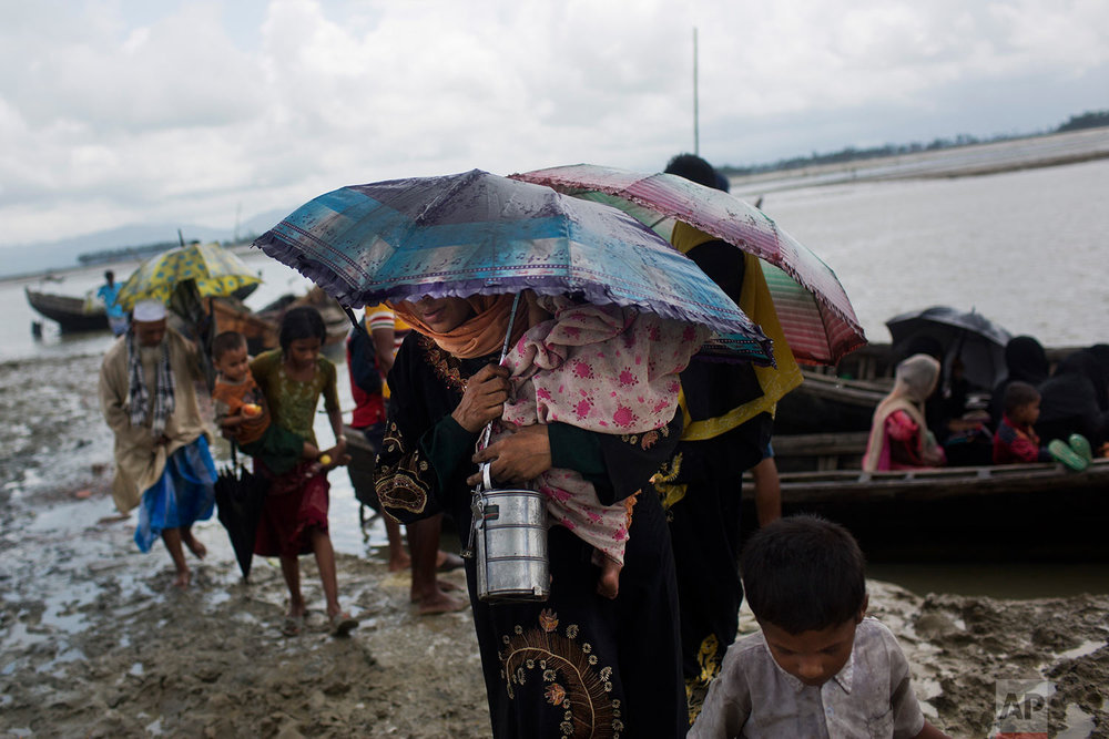 Myanmar's Rohingya ethnic minority walk on a muddy river bank upon crossing a stream on a local boat after crossing over to the Bangladesh side of the border near Cox's Bazar's Dakhinpara area, Saturday, Sept. 2, 2017. (AP Photo/Bernat Armangue)