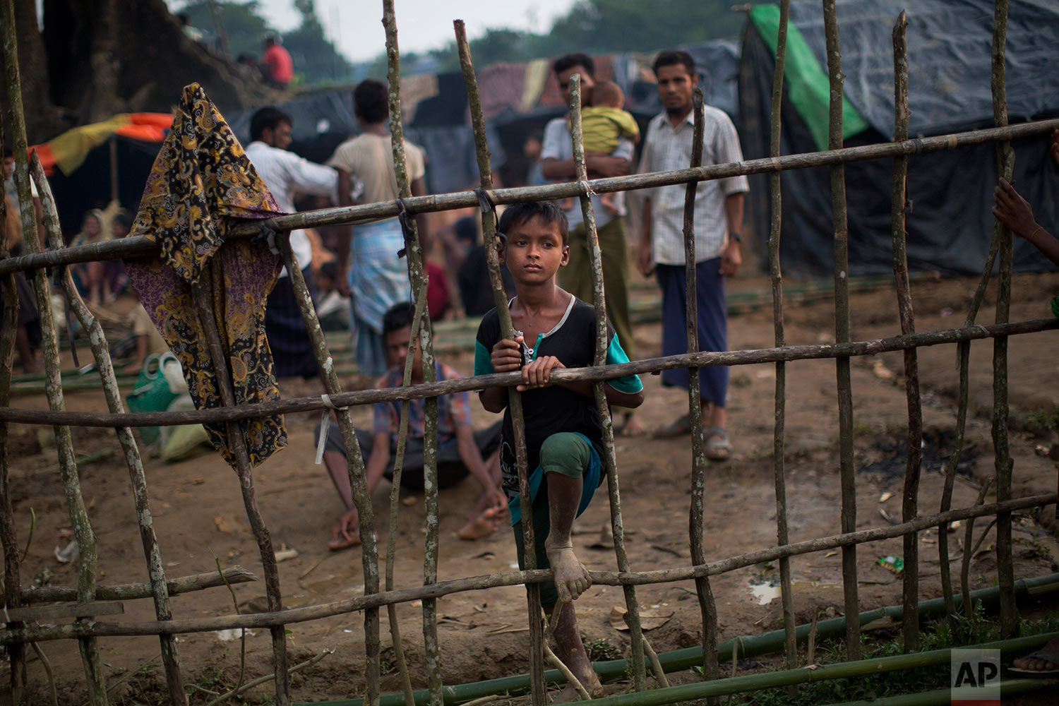 A Rohingya child, newly arrived from Myanmmar to the Bangladesh side of the border, stands by a wooden fence at Kutupalong refugee camp in Ukhia, Tuesday, Sept. 5, 2017. Bangladesh, one of the world's poorest countries, was already sheltering some 100,000 Rohingya refugees before another 123,000 flooded in after Aug. 25, according to the U.N. refugee agency's latest estimate on Tuesday. (AP Photo/Bernat Armangue)