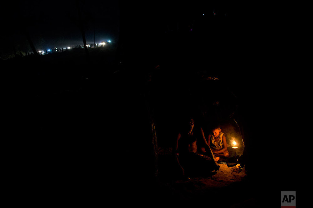 Rohingya Muslims rest inside a new tent next to Kutupalong refugee camp in Ukhia, Bangladesh, Tuesday, Sept. 5, 2017. Bangladesh, one of the world's poorest countries, was already sheltering some 100,000 Rohingya refugees before another 123,000 flooded in after Aug. 25, according to the U.N. refugee agency's latest estimate on Tuesday. (AP Photo/Bernat Armangue)