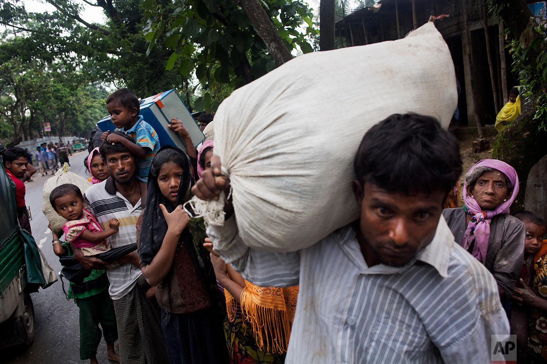 Myanmar's Rohingya ethnic minority refugees walk after crossing the Bangladeshi border near Cox Bazar's Kanjopara area Bangladesh, Sunday, Sept. 3, 2017. (AP Photo/Bernat Armangue)