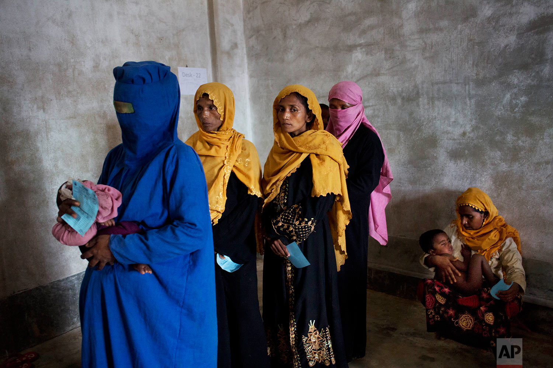Rohingya refugee women carrying their babies wait at a World Food Program distribution center near Kutupalong refugee camp in Ukhia, Bangladesh, Sunday, Sept. 3, 2017. (AP Photo/Bernat Armangue)