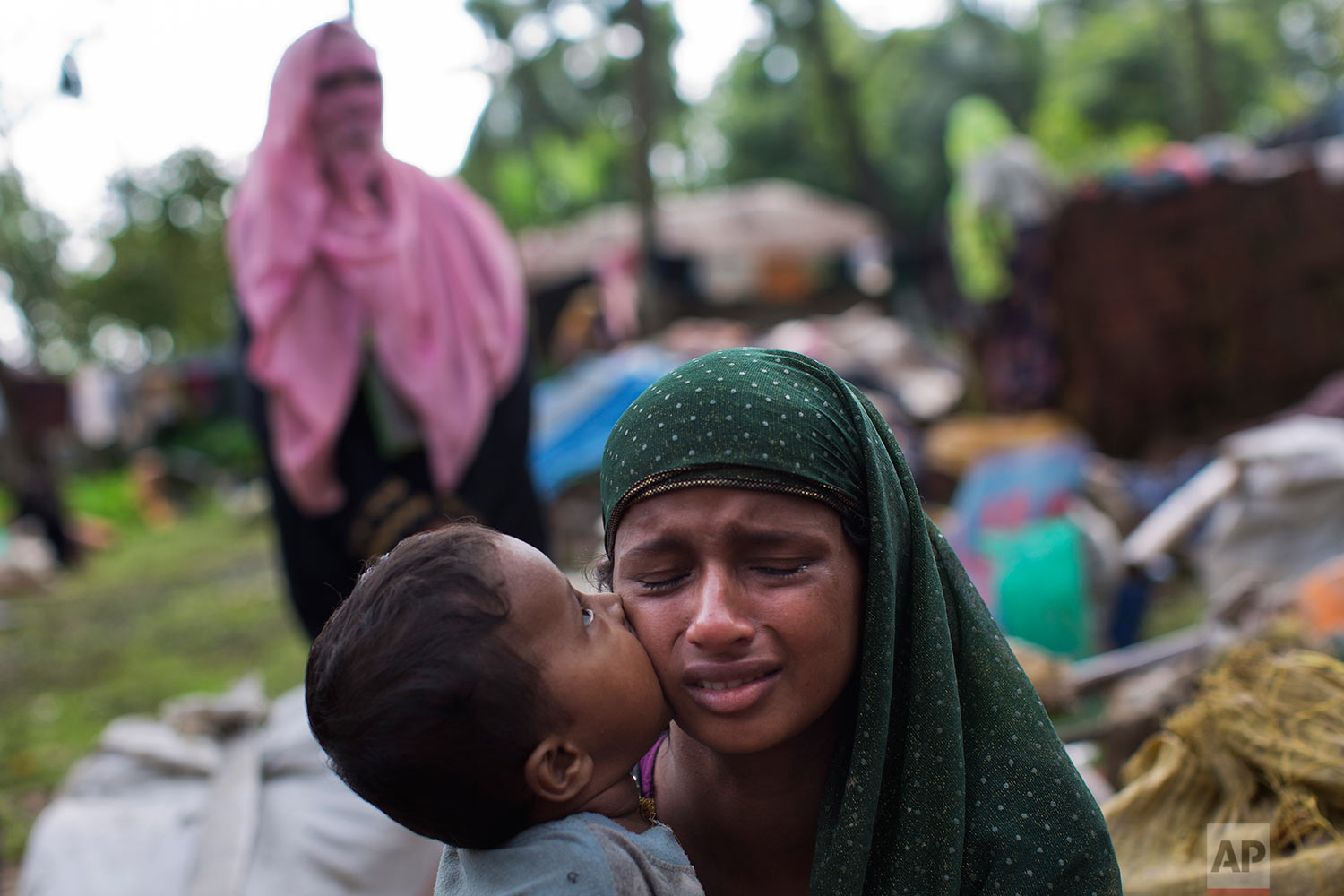 A Rohingya Muslim child places a kiss on his mother's cheek as they rest after having crossed over from Myanmar to the Bangladesh side of the border near Cox's Bazar's Teknaf area, Saturday, Sept. 2, 2017. (AP Photo/Bernat Armangue)