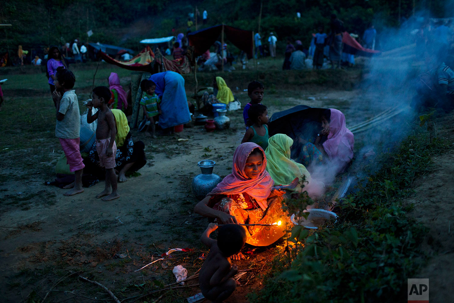 Rohingya ethnic minority, who have just crossed over to Bangladesh from Myanmar, cook a meal near Cox's Bazar's Gundum area, Saturday, Sept. 2, 2017. (AP Photo/Bernat Armangue)