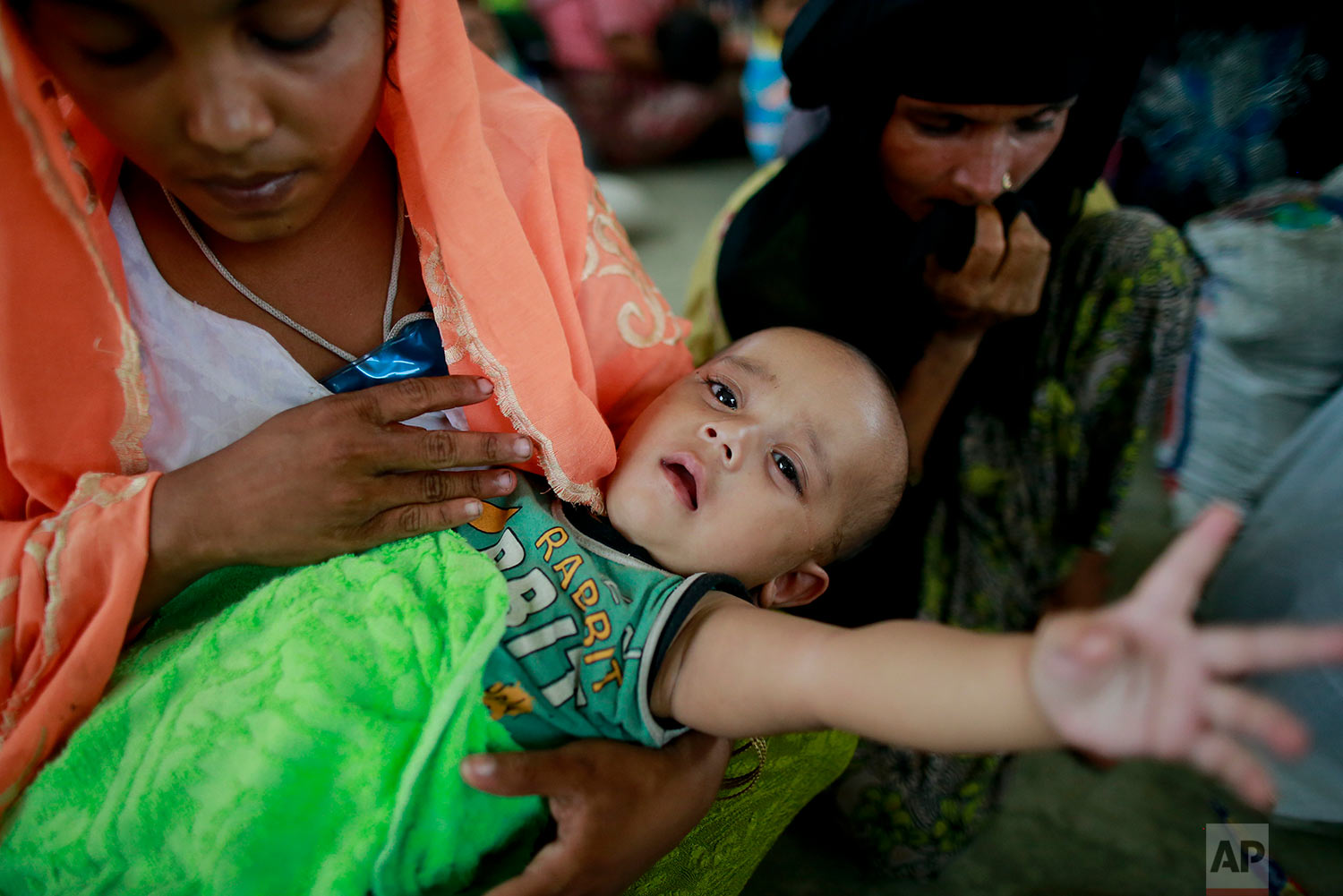 Rohingya woman Rahima, left, sits with her six months old child Jewel at a temporary shelter after being detained by Bangladeshi border guards while crossing the Naf River to enter Bangladesh at Shah Porir Deep, in Teknak, Bangladesh, Thursday, Aug. 31, 2017. Three boats carrying ethnic Rohingya fleeing violence in Myanmar have capsized in Bangladesh and 26 bodies of women and children have been recovered, officials said Thursday. Last week, a group of ethnic minority Rohingya insurgents attacked at least two dozen police posts in Myanmar's Rakhine state, triggering fighting with security forces that left more than 100 people dead and forced at least 18,000 Rohingya to flee into neighboring Bangladesh. (AP Photo/Suvra Kanti Das)