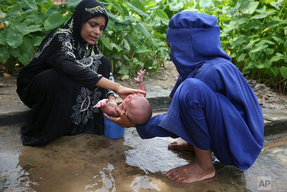 Myanmar's Rohingya Muslim ethnic minority women bathe a week-old infant at the Kutupalong makeshift refugee camp in Cox's Bazar, Bangladesh, Wednesday, Aug. 30, 2017. Thousands of Rohingya Muslims have fled fresh violence in Myanmar and crossed into Bangladesh in less than a week, with hundreds stranded in no man's land at the countries' border, the International Organization for Migration said Wednesday. (AP Photo/Mushfiqul Alam)
