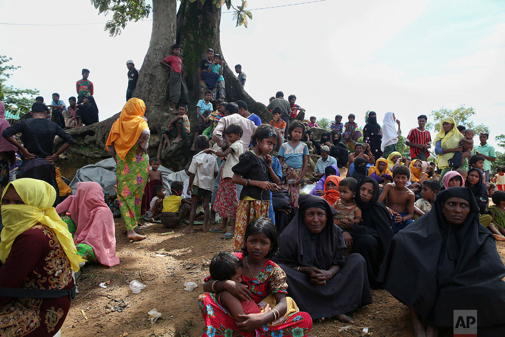 Myanmar's Rohingya Muslim ethnic minority members wait to enter the Kutupalong makeshift refugee camp in Cox's Bazar, Bangladesh, Wednesday, Aug. 30, 2017. Thousands of Rohingya Muslims have fled fresh violence in Myanmar and crossed into Bangladesh in less than a week, with hundreds stranded in no man's land at the countries' border, the International Organization for Migration said Wednesday. (AP Photo/Mushfiqul Alam)