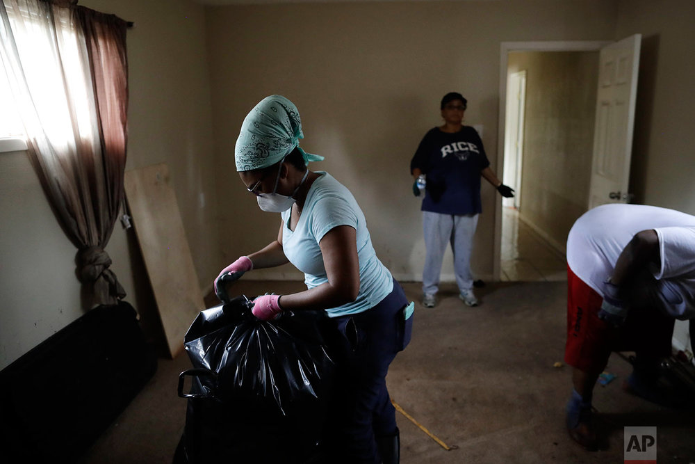 In this Sunday, Sept. 3, 2017, photo, Erica Gradney, left, bags up items in front of Martha Tolfree, center, as they clean up damage to a friend's flooded home in Houston.  (AP Photo/Gregory Bull)