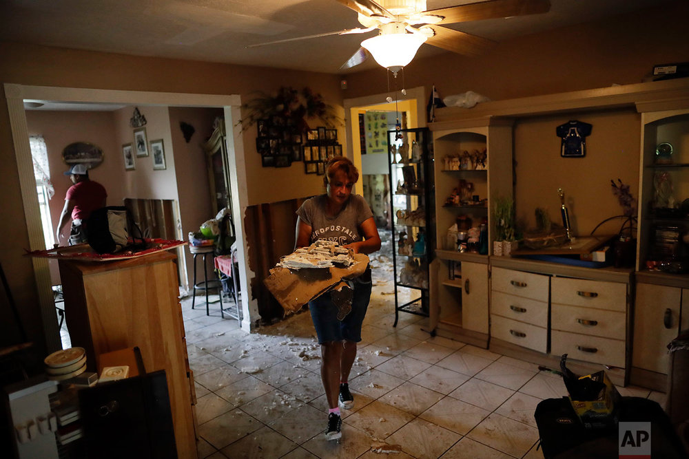 In this Sunday, Sept. 3, 2017, photo, Ana Benavidez carries sections of damaged drywall as she cleans out her flooded home in Houston. (AP Photo/Gregory Bull)