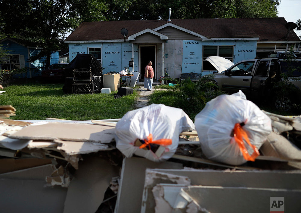 In this Sunday, Sept. 3, 2017, photo, Griselda Perez looks out from behind a wall of flood-damaged debris as the family cleans out their flooded home Sunday, Sept. 3, 2017, in Houston.  (AP Photo/Gregory Bull)