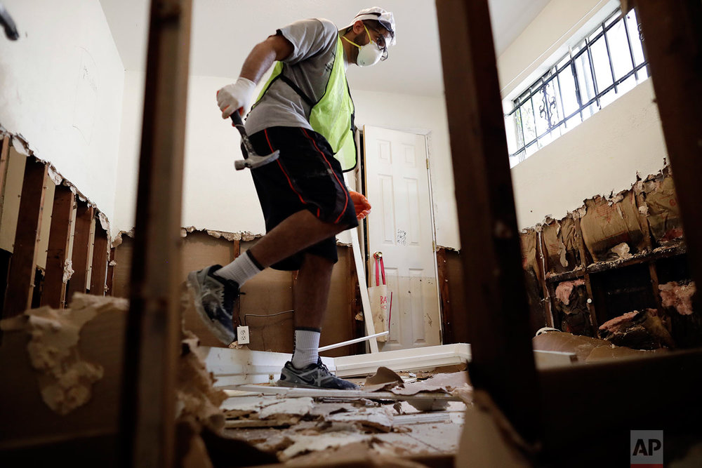 In this Sunday, Sept. 3, 2017, photo, volunteer Hashir Ayubi, of the the Ahmadiyya Muslim Youth Association helps clean out a flood-damaged home in Houston.  (AP Photo/Gregory Bull)