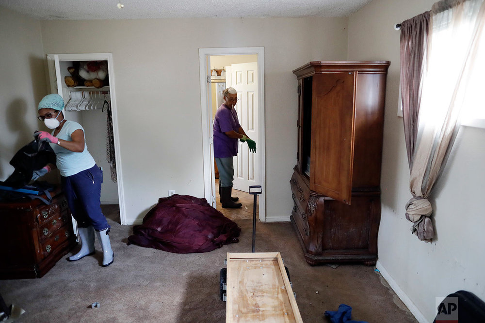 In this Sunday, Sept. 3, 2017, photo, Pauline Simpson, center, gets help from Erica Gradney, left, as they clean up damage to Simpson's flooded home in Houston. (AP Photo/Gregory Bull)