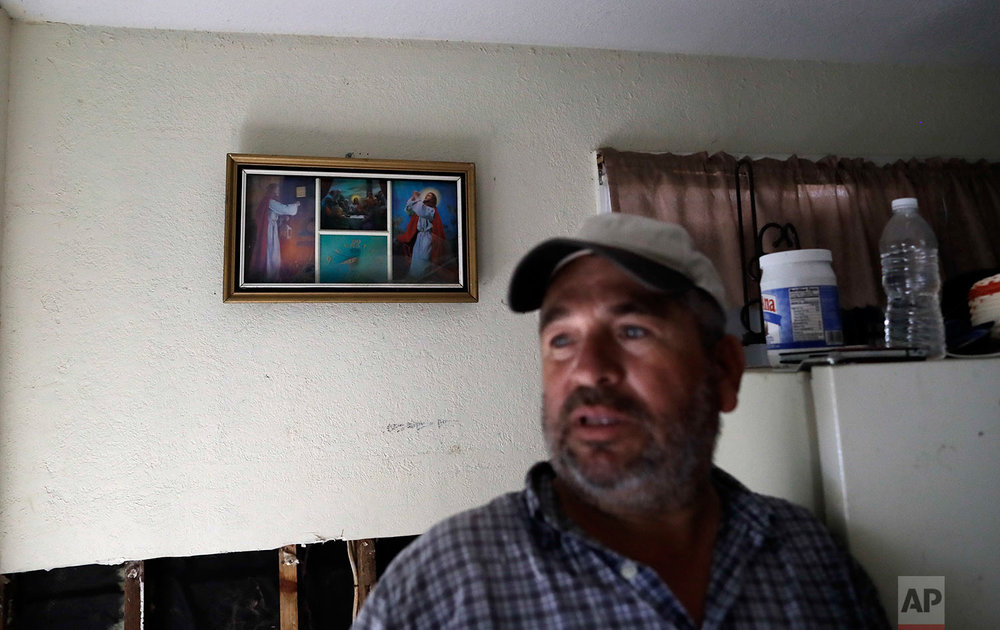 In this Sunday, Sept. 3, 2017, photo, religious images are almost all that still hang on the walls of Lino Saldana's home, as he talks about the floodwaters from a nearby bayou that swept through his home in Houston. Like many of his neighbors on flood-ravaged Minden Street, Saldana knows that if he doesn't work, he doesn't get paid. (AP Photo/Gregory Bull)