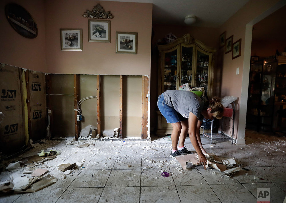 In this Sunday, Sept. 3, 2017, photo, Ana Benavidez picks up damaged drywall as she cleans out her flooded home in Houston. (AP Photo/Gregory Bull)