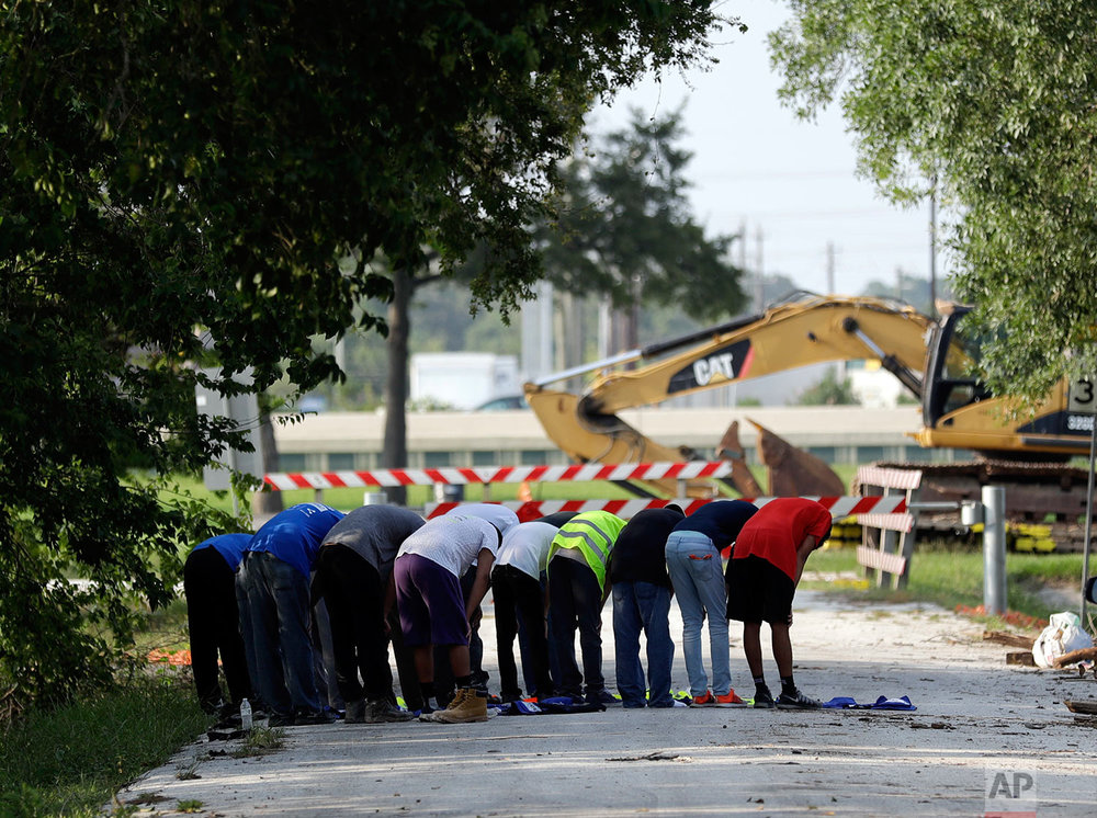 In this Sunday, Sept. 3, 2017, photo, volunteers from the Ahmadiyya Muslim Youth Association take a moment to pray as they help families clean out their flood-damaged homes in Houston. (AP Photo/Gregory Bull)