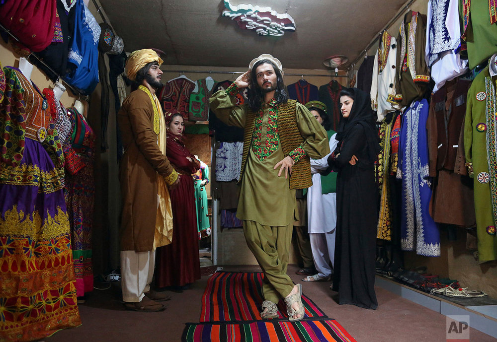 Omid Arman, center, a model for traditional embroidered Afghan clothing, practices modeling, in Kabul, Afghanistan on Aug. 3, 2017. His employer, Ajmal Haqiqi, who hails from the restive Ghazni province, said he exhibits and markets the traditional clothing in hopes of preserving Afghanistan's 5,000-year-old culture. (AP Photo/Rahmat Gul)