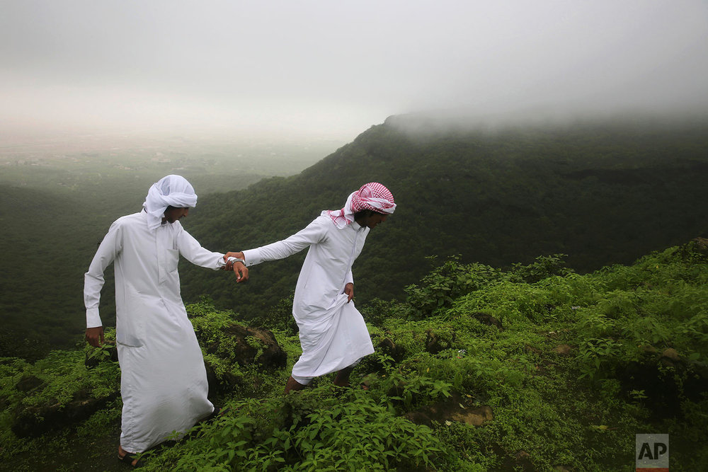 Mohammad al-Bariki, right, 17, leads his half-brother Sagheer al-Bariki, 17, across a cliff ledge in the Jabal Ayoub mountains north of Salalah, Oman on Aug. 2, 2017. (AP Photo/Sam McNeil)