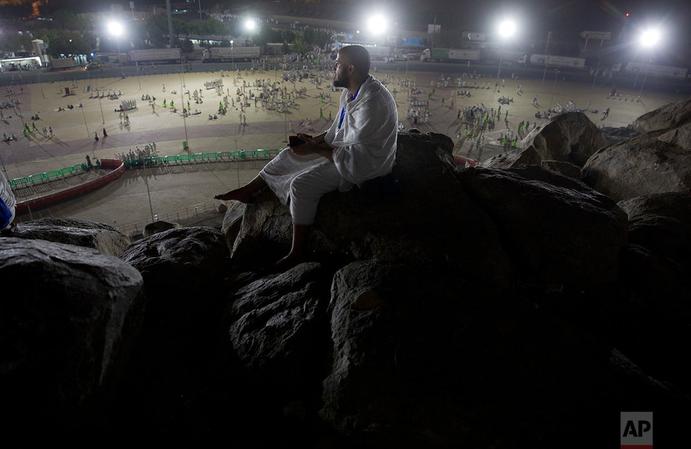 A Muslim pilgrim prays on top of the Jabal Al Rahma holy mountain, or the mountain of forgiveness, upon their arrival to Arafat for the annual hajj pilgrimage, outside the holy city of Mecca, Saudi Arabia, Wednesday, Aug. 30, 2017. (AP Photo/Khalil Hamra)