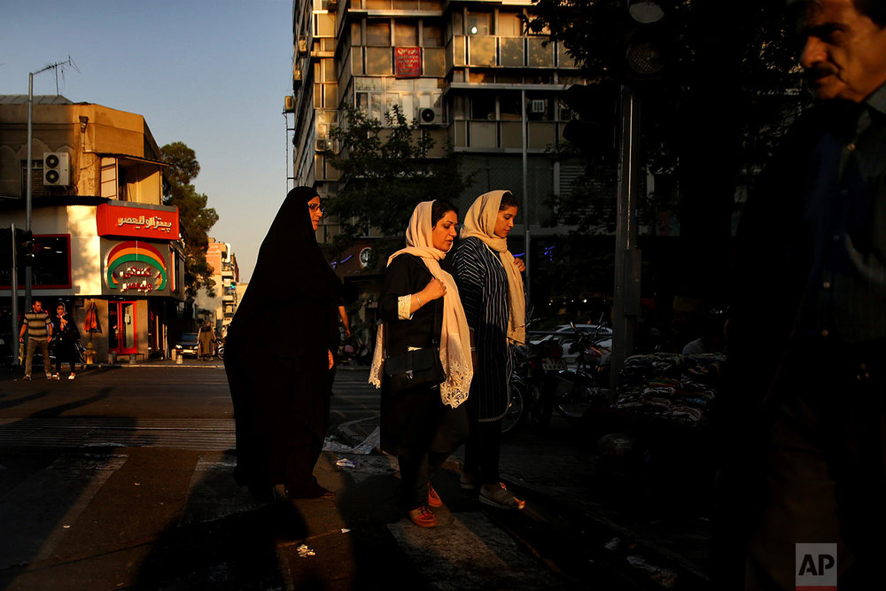 "Iranian women cross a street while one of them wears the ""chador"" in downtown Tehran, Iran on Aug. 24, 2017. (AP Photo/Vahid Salemi)"