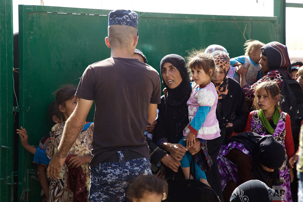 An Iraqi policeman gestures at a group of displaced women and children at a collection point west of Mosul on the outskirts of Tal Afar, Iraq, Saturday, Aug. 26, 2017. The Iraqi military said on Saturday that they had taken 90 percent of the town, one of the last bastions of the Islamic State group in northern Iraq. (AP Photo/Balint Szlanko)
