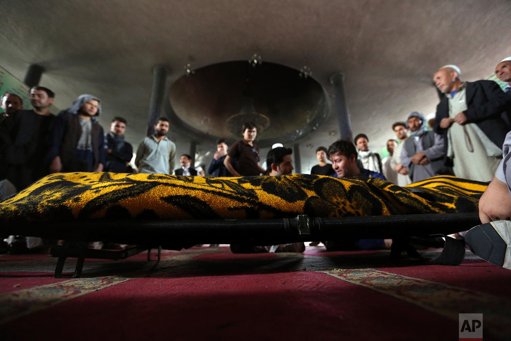 Men stand near the coffin of a relative who died in a Shiite mosque attack, Saturday, Aug. 26, 2017, in Kabul, Afghanistan. Dozens of people, including women and children, were killed in an attack on a Shiite mosque in the Afghan capital during Friday prayers. (AP Photo/Rahmat Gul)