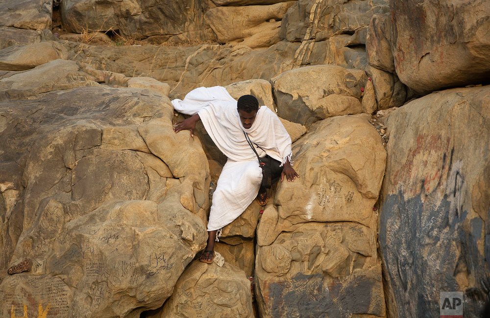 A pilgrim climbs Jabal Al Rahma holy mountain, or the mountain of forgiveness, at Arafat for the annual Muslim hajj pilgrimage outside the holy city of Mecca, Saudi Arabia, Thursday, Aug. 31, 2017. (AP Photo/Khalil Hamra)