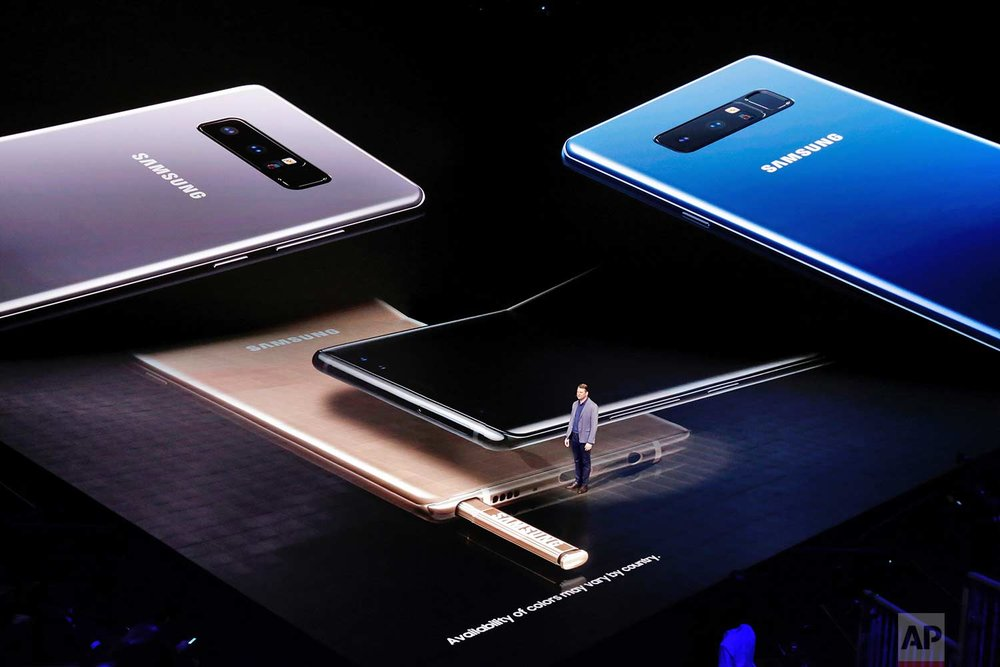 Justin Denison, vice president of strategy for Samsung Telecommunications America, stands among projections of the company's Galaxy Note 8, during the phone's introduction, in New York, Wednesday, Aug. 23, 2017. (AP Photo/Richard Drew)