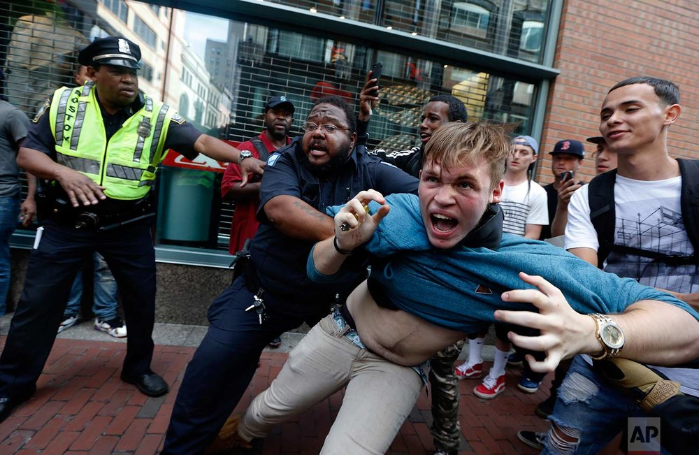 "A counter-protester, part of a small group who remained on the street hours after a ""Free Speech"" rally was staged by conservative activists, scuffles with a security guard and police, Saturday, Aug. 19, 2017, in Boston. (AP Photo/Michael Dwyer)"