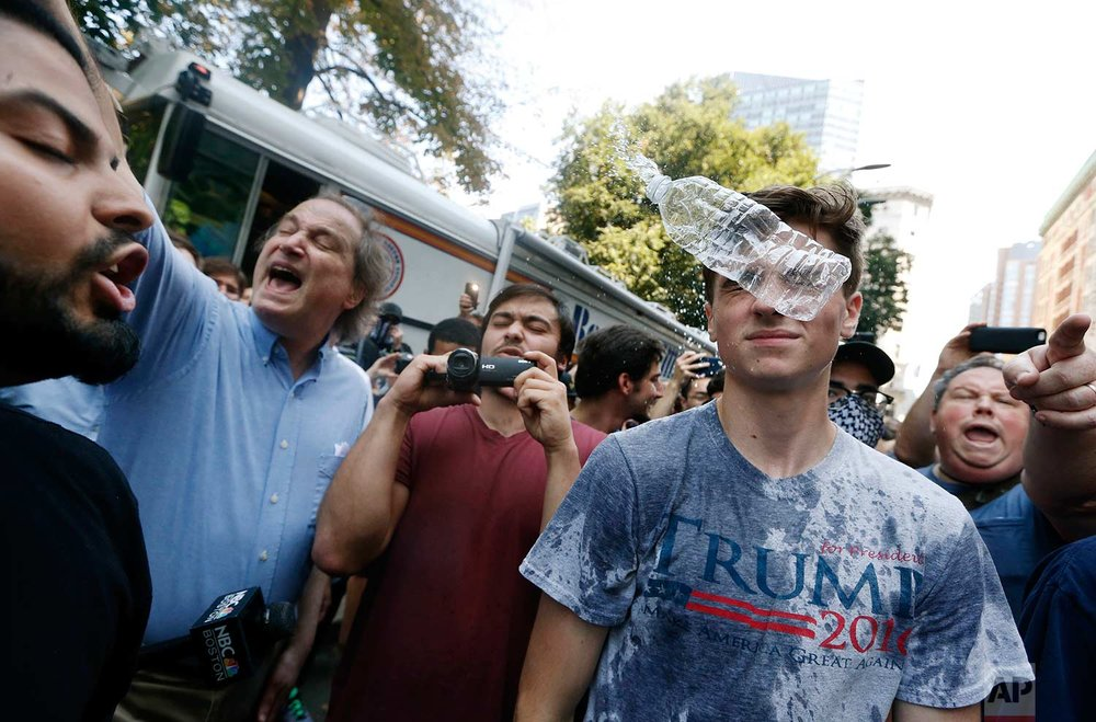 "A man wearing a T-shirt bearing the name of President Donald Trump, right, is hit by a flying plastic bottle of water near a ""Free Speech"" rally staged by conservative activists, Saturday, Aug. 19, 2017, in Boston. Counterprotesters marched through the city to historic Boston Common, where many gathered near a bandstand abandoned early by conservatives who had planned to deliver a series of speeches. (AP Photo/Michael Dwyer)"