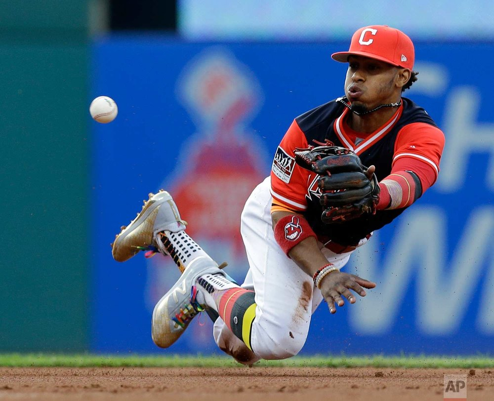 Cleveland Indians' Francisco Lindor tosses the ball from his mitt to second baseman Jose Ramirez to get Kansas City Royals' Lorenzo Cain out at second base during the first inning of a baseball game, Friday, Aug. 25, 2017, in Cleveland. (AP Photo/Tony Dejak)
