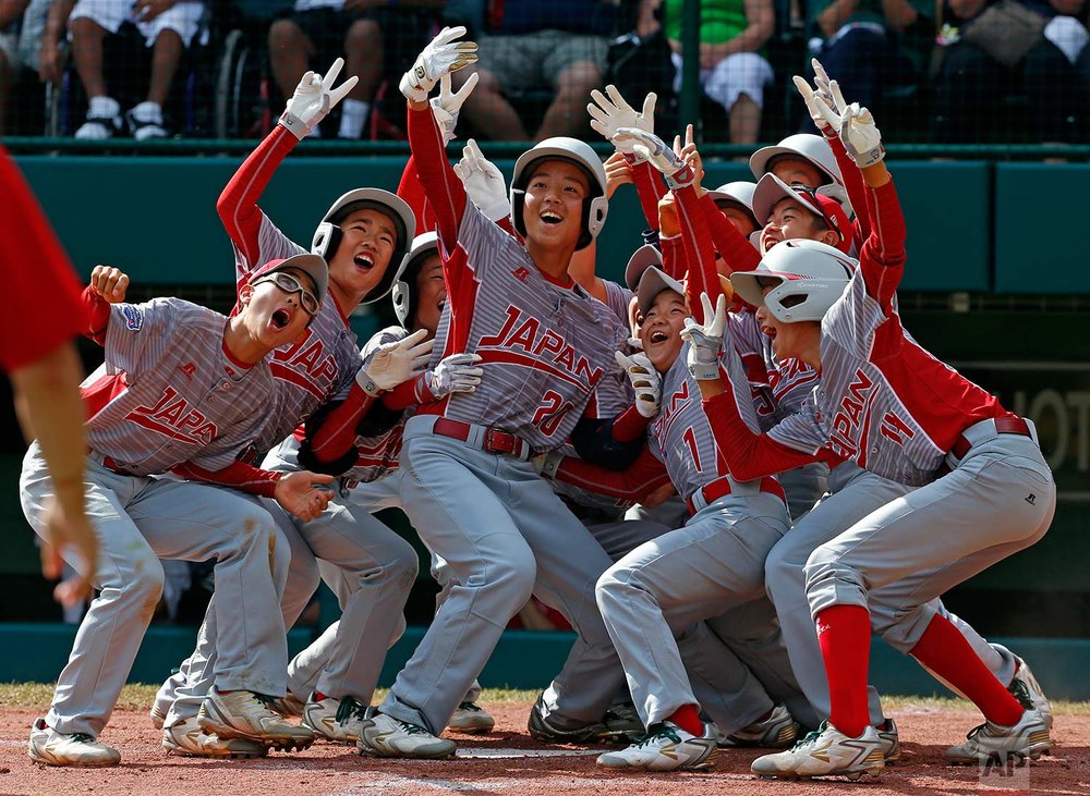 Tokyo, Japan's Natsuki Yajima (20) celebrates with teammates after hitting a two-run home run off White Rock, British Columbia pitcher Reece Ussleman in the third inning of an International baseball game at the Little League World Series tournament in South Williamsport, Pa., Wednesday, Aug. 23, 2017. Japan won 10-0. (AP Photo/Gene J. Puskar)