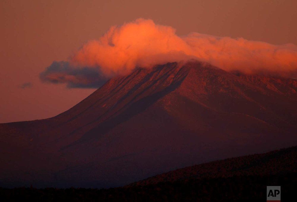 In this Monday, Aug. 7, 2017 photo, the first rays of sunlight color the clouds over Mount Katahdin in this view from the Katahdin Woods and Waters Scenic Byway outside Patten, Maine. Interior Secretary Ryan Zinke wants to retain the newly created national monument, but said he might recommend adjustments to the White House on Thursday, Aug. 24, 2017. (AP Photo/Robert F. Bukaty)