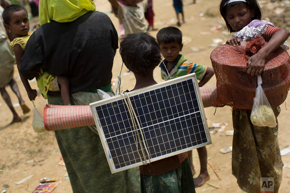 In this Thursday, Sept. 7, 2017, photo, a Rohingya Muslim child carries a solar panel as she crosses over the border from Myanmar into Bangladesh in Teknaf area. (AP Photo/Bernat Armangue)