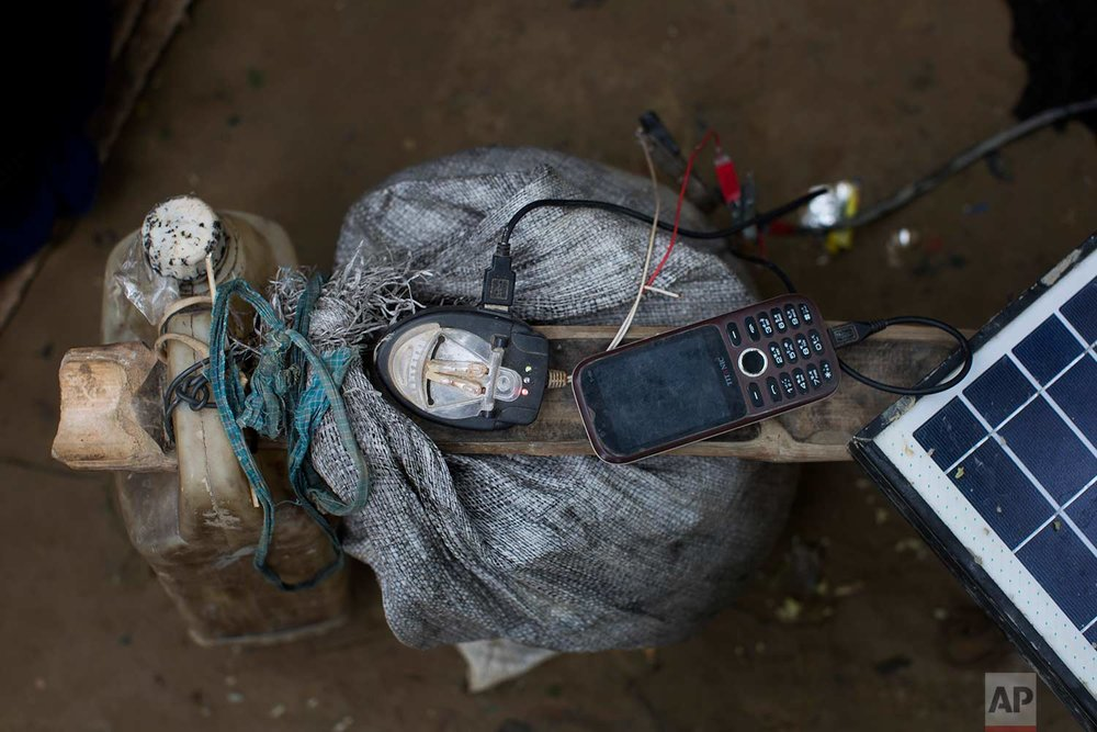 In this Thursday, Sept. 7, 2017, photo, a mobile phone is charged by a solar panel brought across the border by a Rohingya in Teknaf area, Bangladesh. (AP Photo/Bernat Armangue)