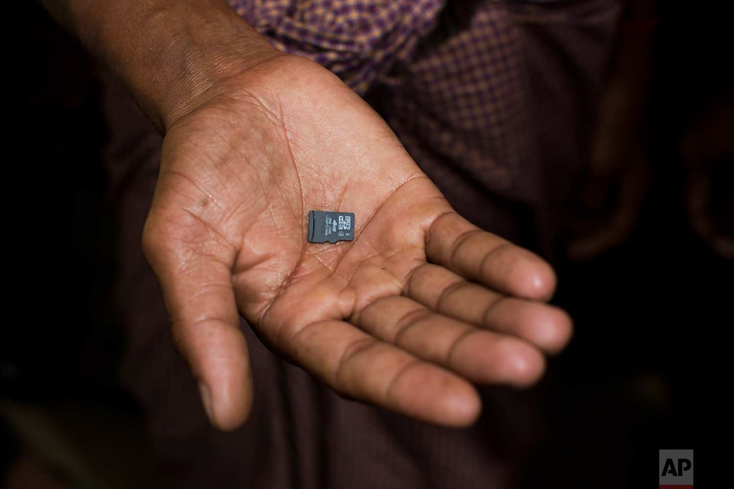 In this Thursday, Sept. 7, 2017, photo, a Rohingya Muslim displays a memory card carried across the border from Myanmar into Bangladesh in Teknaf area. Cellphones to reach out to separated relatives, bags of spices that remind them of home and solar panels to bring a little light to their ragged tents are some of the things the exhausted Rohingya Muslims carry with them as they escape the violence that they've endured in Myanmar's Rakhine state over the last two weeks. Those who don't carry phones still often bring memory cards from their abandoned ones. (AP Photo/Bernat Armangue)