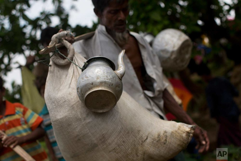 In this Thursday, Sept. 7, 2017, photo, a Rohingya Muslim man arrives with a sack of belongings and a kettle tied to a stick as he crosses the border into Bangladesh's Teknaf area. (AP Photo/Bernat Armangue)