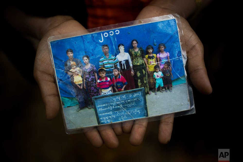 Rohingya Mubarak Begum, who crossed over from Myanmar into Bangladesh, holds a photograph of her family members, in Kutupalong, Bangladesh, Friday, Sept. 8, 2017.  (AP Photo/Bernat Armangue)
